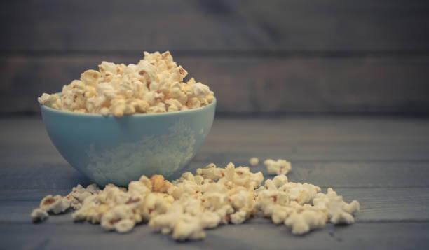 Popcorn in einer Schüssel auf einem Holztisch – Foto
