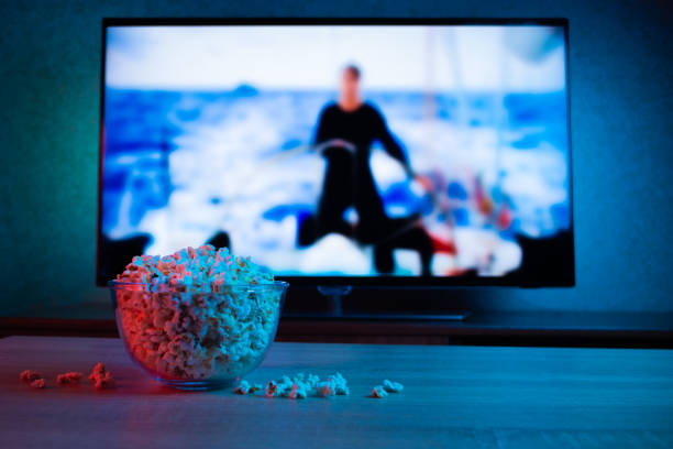 Popcorn in a glass plate on the background of the TV. Color bright lighting, blue and red. Background Popcorn in a glass plate on the background of the TV. Color bright lighting, blue and red. Background watching tv stock pictures, royalty-free photos & images