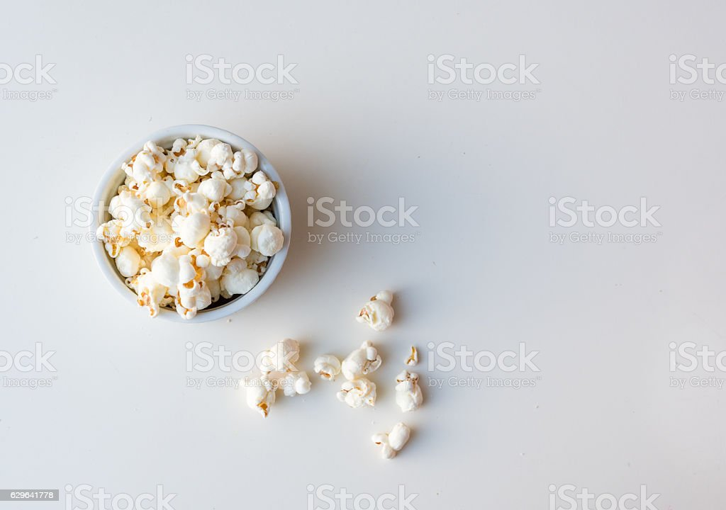 Popcorn in dish and on table from above stock photo