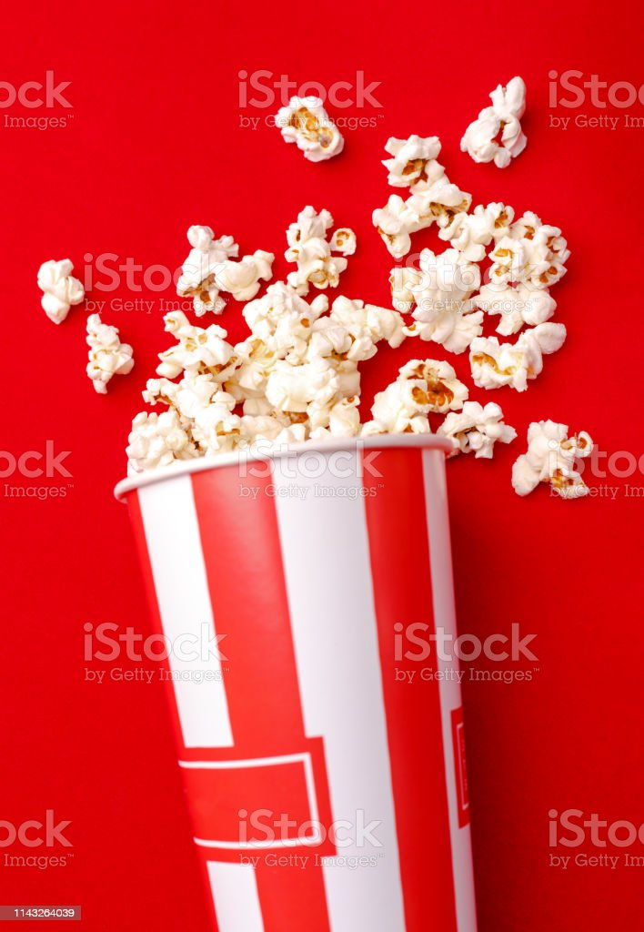 Popcorn in red and white cardboard box. Popcorn border isolated on...