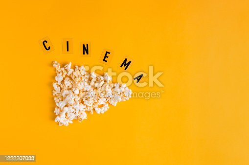 istock Popcorn in the shape of play button and text CINEMA on yellow background. Flat lay banner, top view. To go to the cinema concept. I like watching films. 1222207033