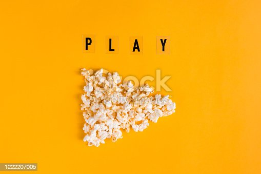 istock Popcorn in the shape of play button and text PLAY on yellow background. Flat lay banner, top view. To go to the cinema concept. I like watching films. 1222207005