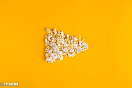 istock Popcorn in the shape of play button on yellow background. Flat lay banner, top view. To go to the cinema concept. I like watching films. 1222206869