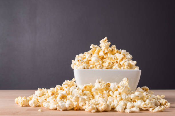 Popcorn in white bowl on wood background stock photo