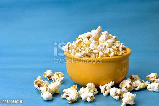 popcorn inside bowl with pink bottom with corn beside on blue background
