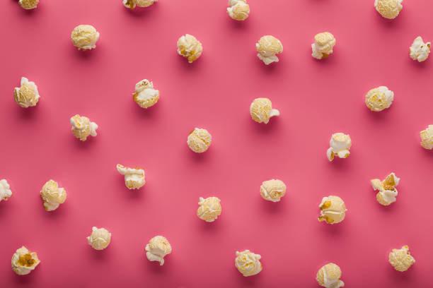 popcorn auf einem rosa hintergrund - popmusiker stock-fotos und bilder