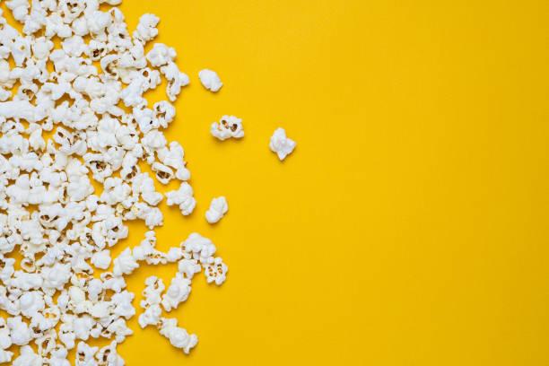 popcorn op een gele rug - popcorn stockfoto's en -beelden