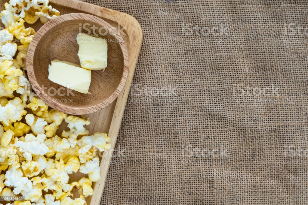 popcorn on wooden plate with butter in wooden bowl on gunny sack cloth stock photo