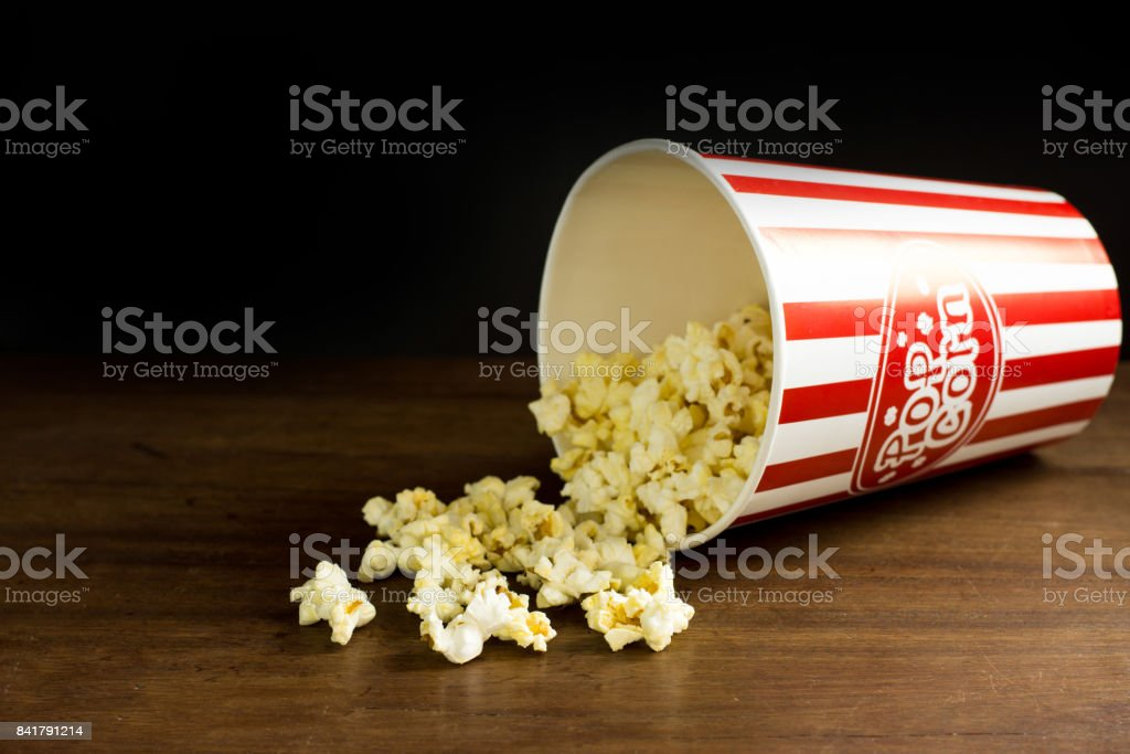 Popcorn on wooden table .Red and white striped  box of popcorn for movie ,Word of popcorn on the bucket stock photo