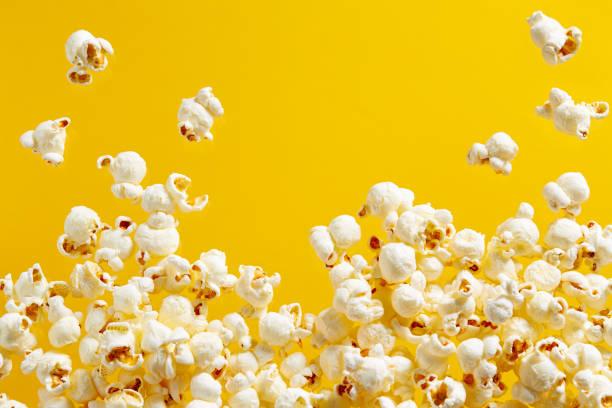 popcorn op gele achtergrond - popcorn stockfoto's en -beelden