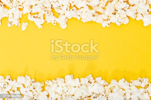 Popcorn on yellow background. Movie or TV background, border, frame. Top view Copy space