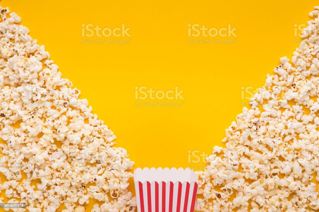 Popcorn on yellow background, top view royalty-free stock photo