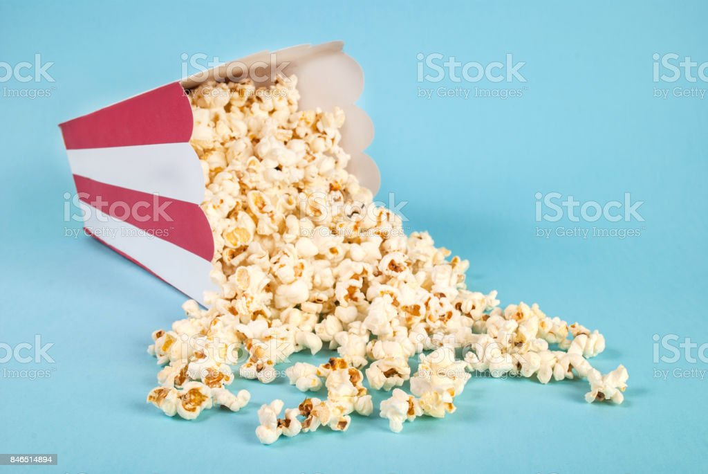 Popcorn spilled on blue background stock photo