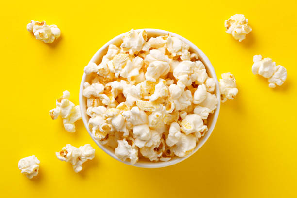 Popcorn viewed from above on yellow background. Flat lay of pop corn bowl. Top view stock photo