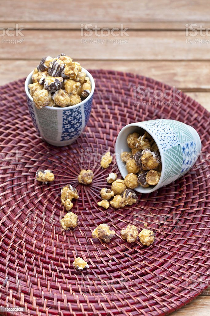 Popcorn with caramel and chocolate in  bowls on wooden surface. royalty-free stock photo