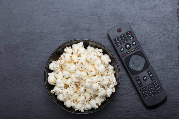 Popcorn with TV remote controler stock photo