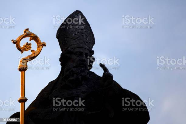 Pope blesses with two fingers the sign of the cross. Statue on the Charles Bridge in Prague
