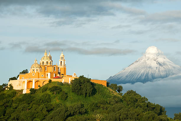 Popocatepetl - Smoking mountain View of Popocatepetl volcano, with the church of Nuestra Señora de los Remedios at the front. City of Cholula, Mexico. puebla state stock pictures, royalty-free photos & images