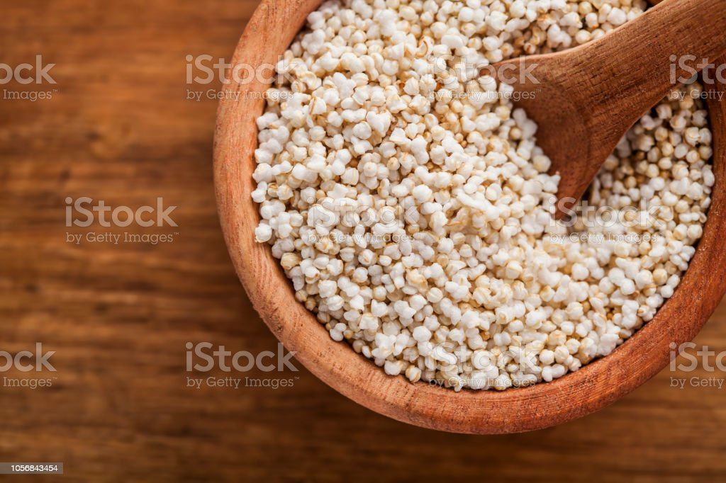 popped amaranth in wooden bowl and background stock photo