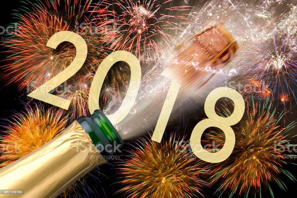 popping champagne and fireworks at new years eve and silvester 2018
