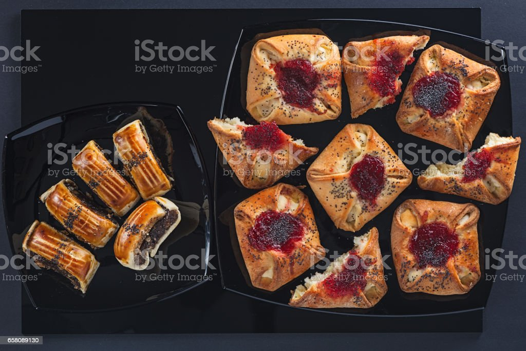 Poppy and jam cakes of a different form on small and big square ceramic plates стоковое фото