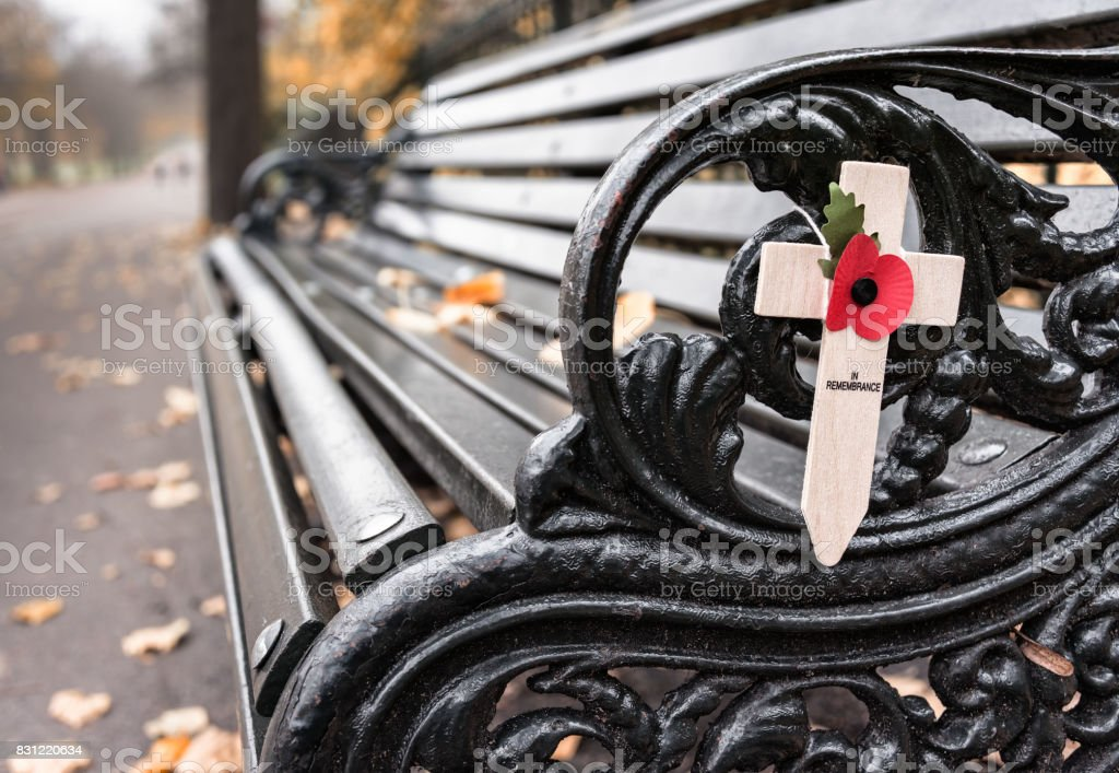 Poppy appeal remembrance cross on cast iron bench (Rememberance Day) stock photo