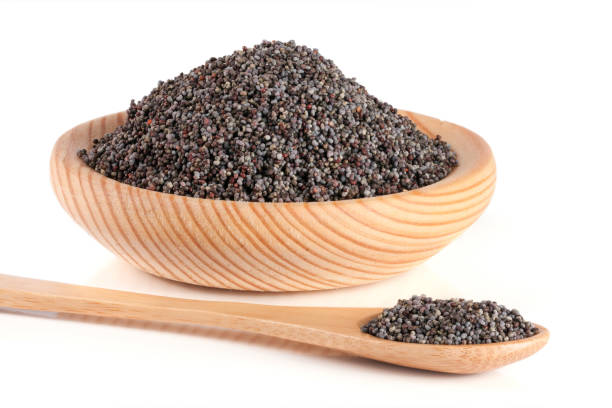poppy seeds in a wooden bowl and spoon isolated on white background stock photo