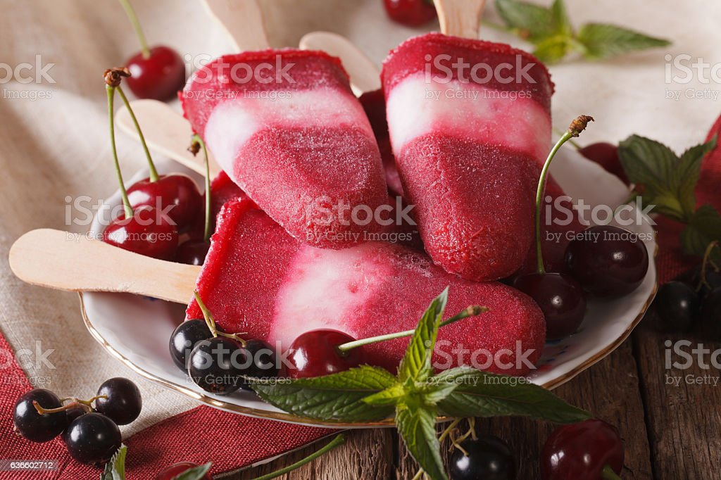 Popsicle with mint and cherry on a stick close-up stock photo