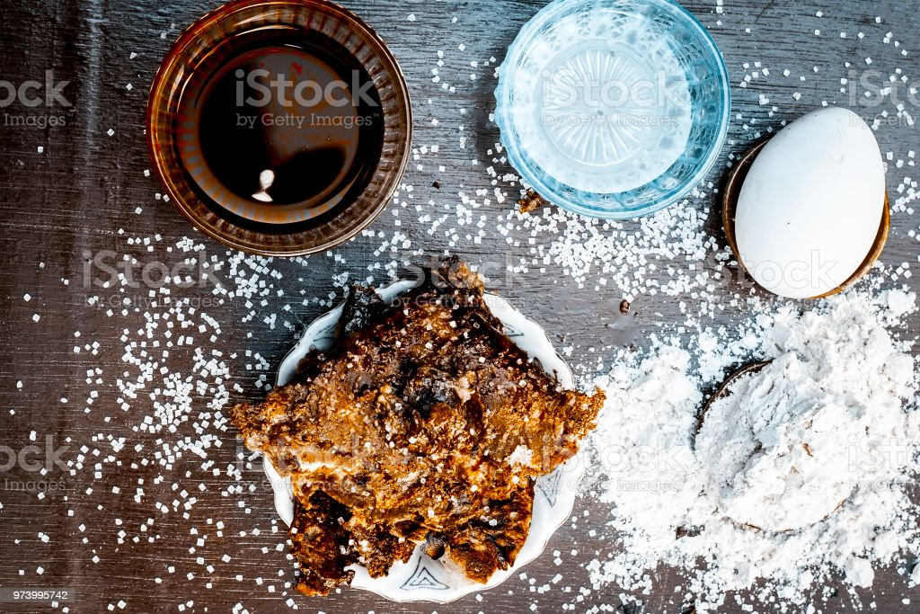 Popular Asian/Indian Ramzan special dish i.e. METHA CHILLA or sugared chapati with ghee and all its ingredients which are egg,sugar,honey and pure ghee on a wooden surface in dark Gothic colors. stock photo