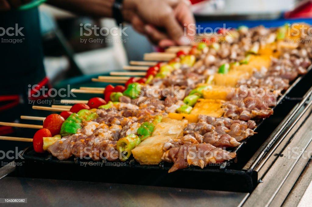 Un asado popular con carne de cerdo filete, tomate, al gusto y parrilla, bar-b-q en parrilla caliente - foto de stock