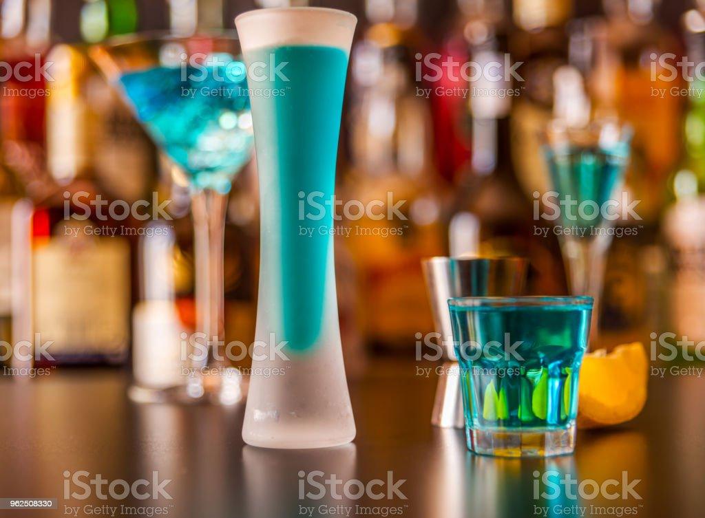 Bebida popular azul atirou kamikaze no fundo do bar com garrafas, uma bebida refrescante - Foto de stock de Azul royalty-free