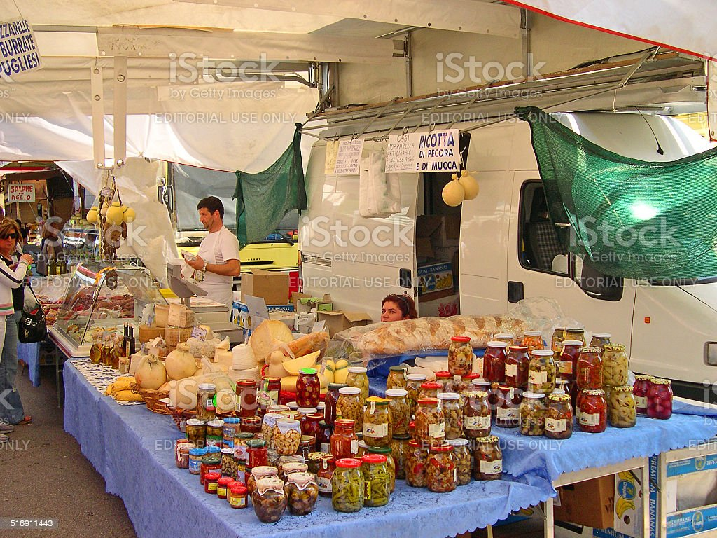 vendor at a cheese and preserved food stand at the Wednesday outdoor...
