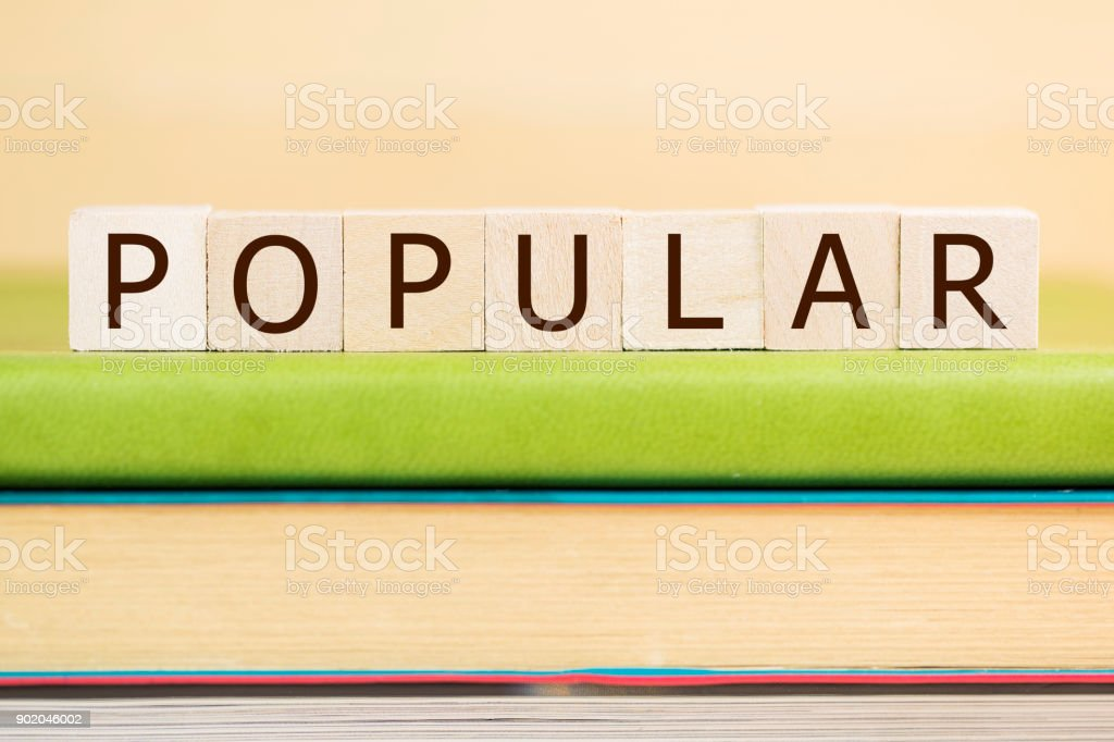 Popular word built with letter cubes on green book stock photo
