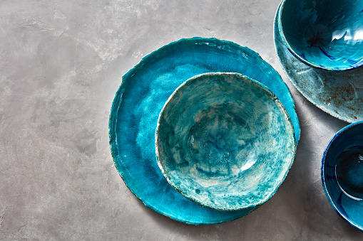 Porcelain blue bowls and plates on a gray table . Colorful ceramic vintage handmade dishes. Flat lay