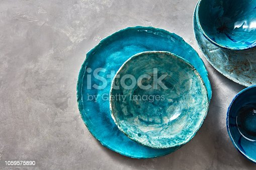 Decorative pottery - bowls, plates covered with glazed on a gray background, place for text. Top view of traditional handcrafted.