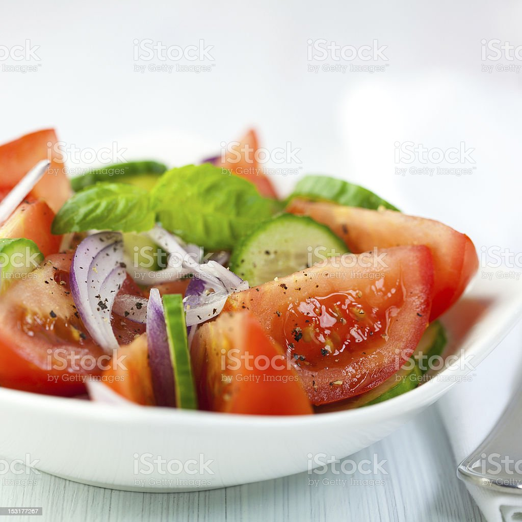 Porcelain bowl of tomato and cucumber salad stock photo