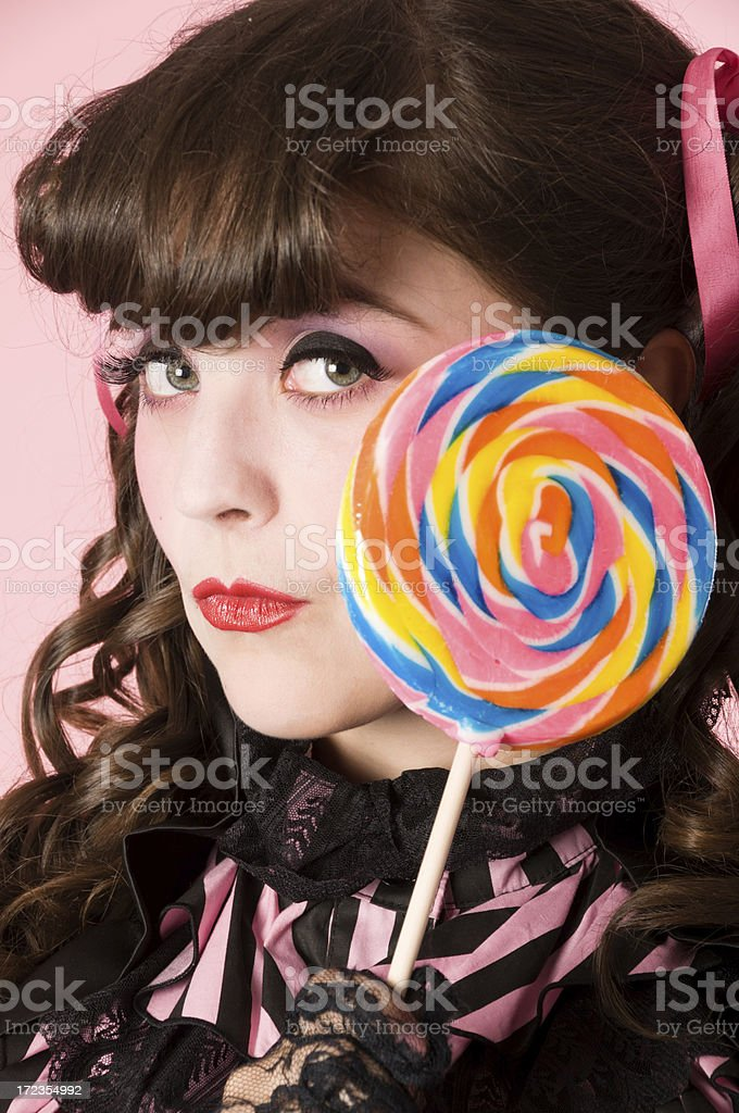 Porcelain doll model in profile with colourful lollipop. royalty-free stock photo