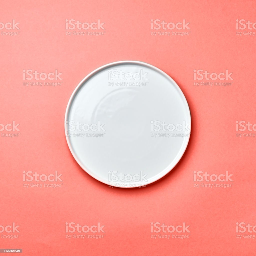 Porcelain empty round handmade a plate on a background in color of the year 2019 Living Coral pantone with a copy of space. Flat lay stock photo