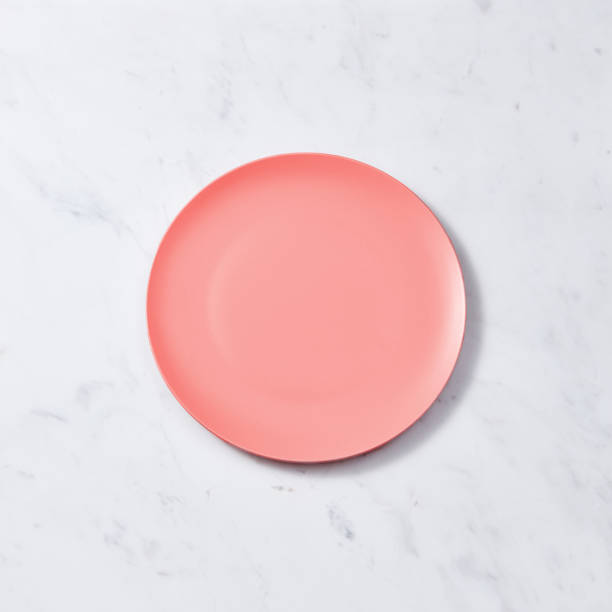 Porcelain handmade empty plate in a color of the year 2019 Living Coral pantone on a gray marble table, place for text. Flat lay stock photo
