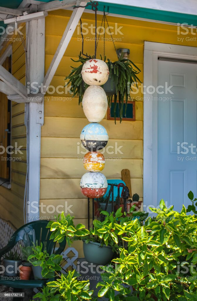 Porch and entrance to local yellow wooden Key West home with bouys and plants hanging  by door stock photo