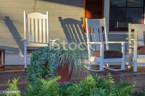 White rocking chairs set amid potted plants on a front porch in afternoon or morning sun express an open invitation to sit and relax.