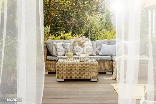 Cozy porch with wooden floor, coffee table and comfortable sofa