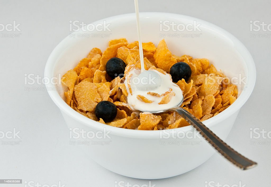 Poring milk into bowl of cereal stock photo