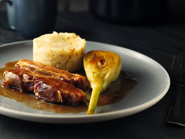 panceta de cerdo con patatas hechas e hinojo estofado - tocino fotografías e imágenes de stock