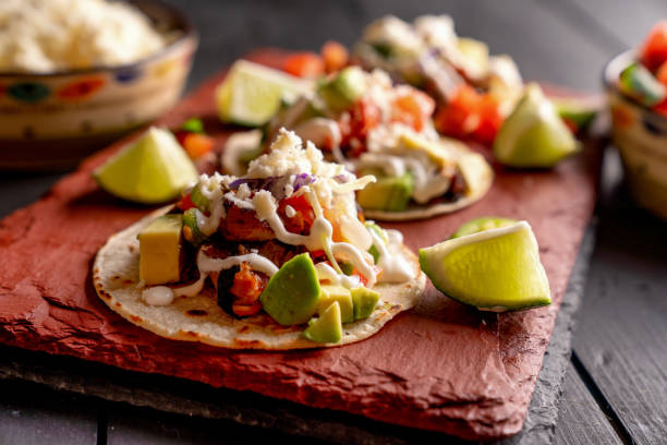 Pork Carnitas Tacos on a Rustic Slate Ready to be Served with Peppers, Lime, Salsa and Cotija Cheese stock photo