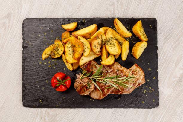 schweinekoteletts in honigsauce mit gerösteten kartoffeln - schnitzel braten stock-fotos und bilder