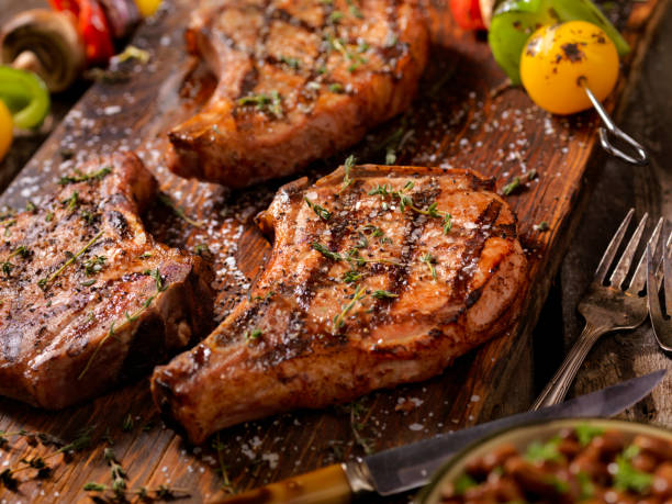 BBQ Pork Chops With Vegetable Skewers BBQ Pork Chops With Vegetable Skewers, Baked Beans and Coleslaw pork stock pictures, royalty-free photos & images