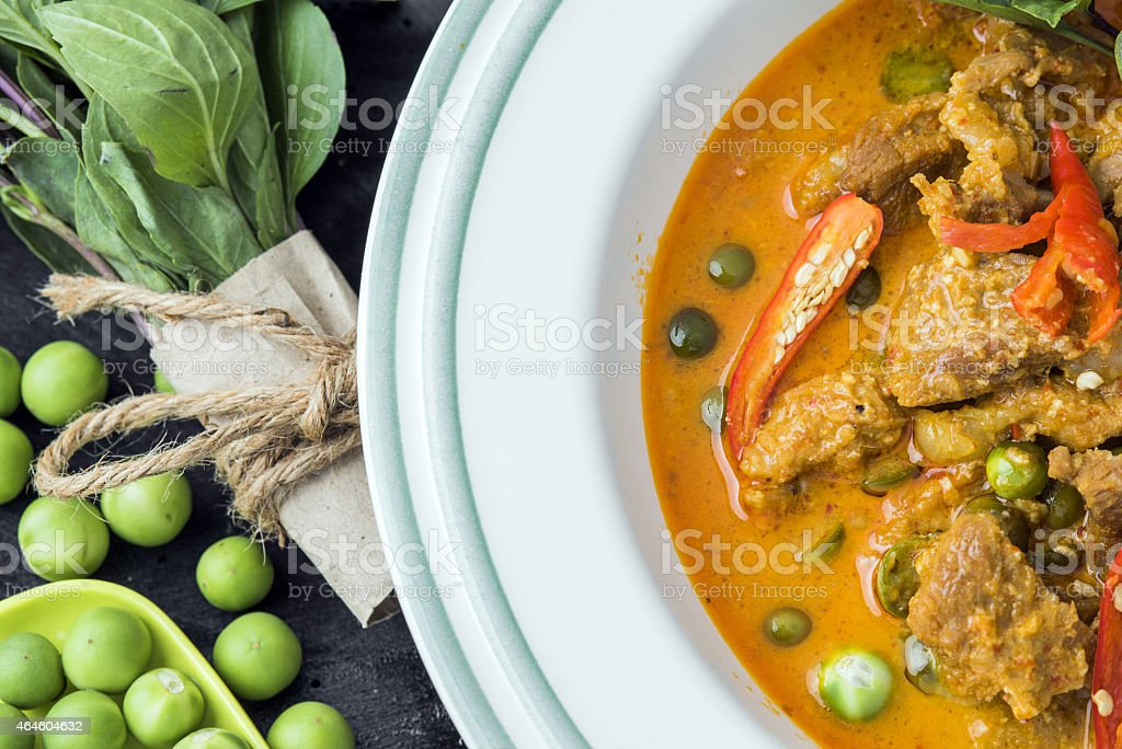 A pork curry on a plate with peas and chili stock photo