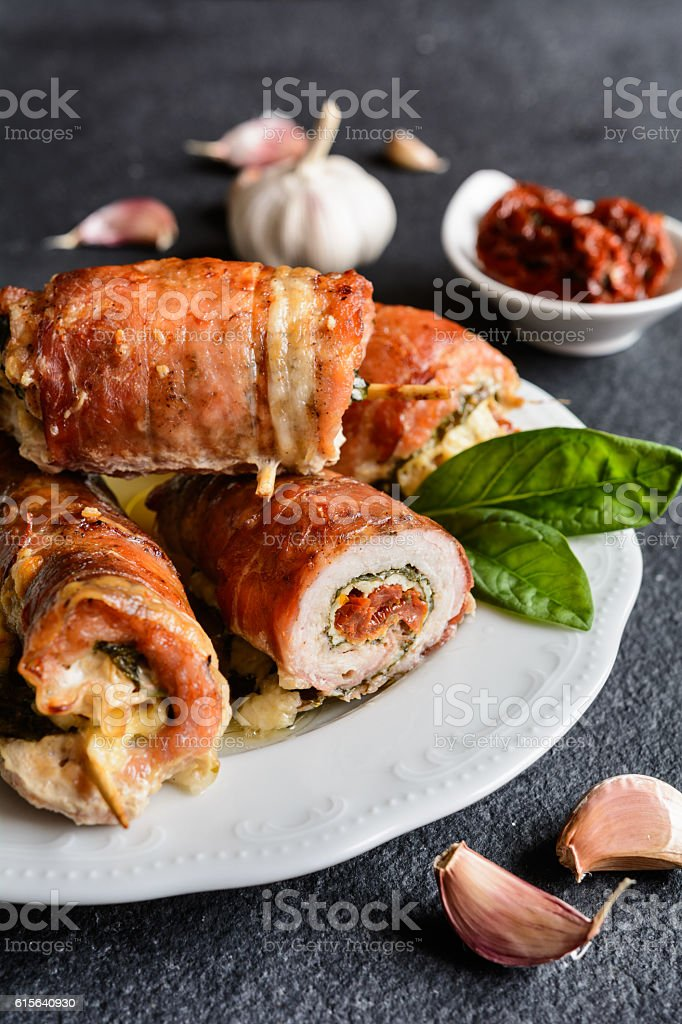 Pork cutlets wrapped in bacon, stuffed with cheese and spinach stock photo