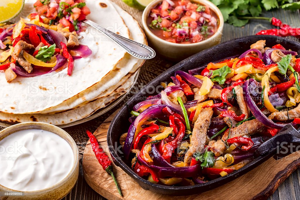 Pork fajitas with onions and colored pepper, served with tortill stock photo